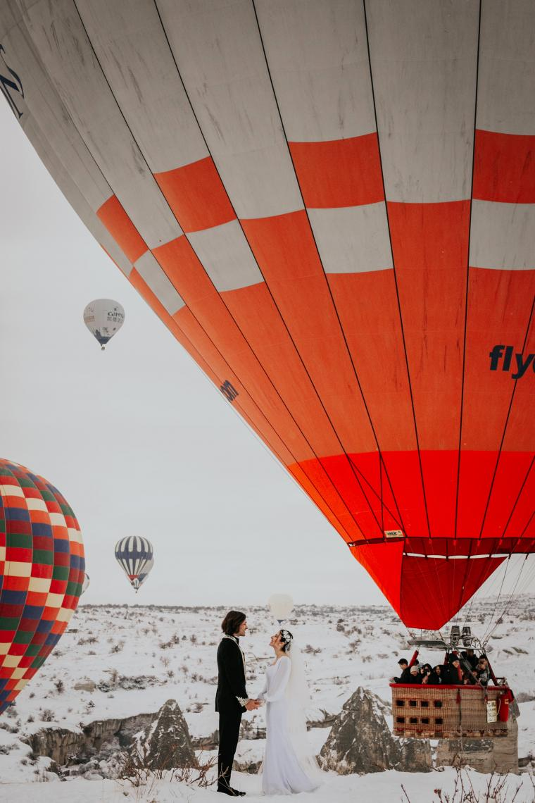 Wedding couple in snowy landscape with hot air balloons