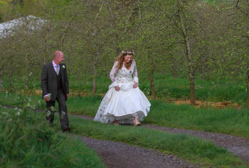 Bride and groom walking through the cider orchard