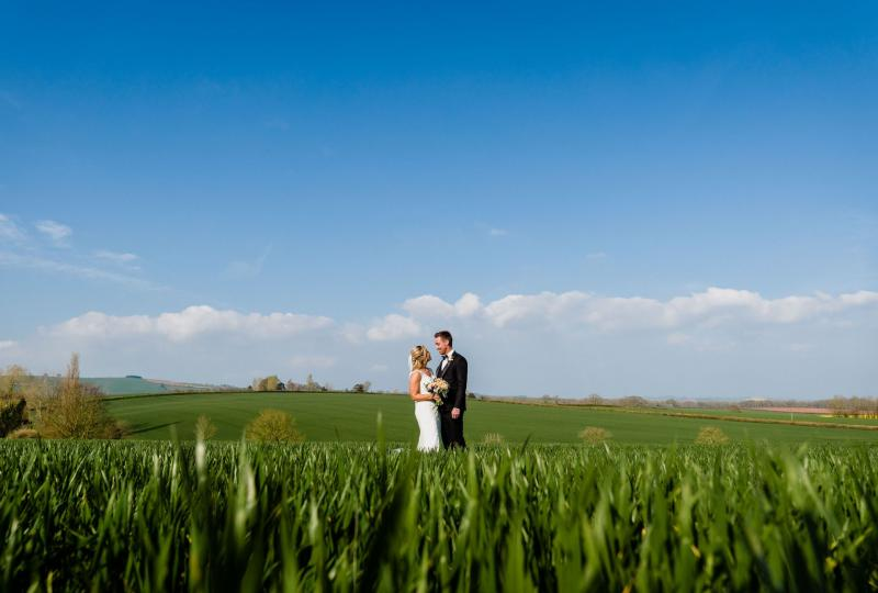 Couple in wheat field under blue skies