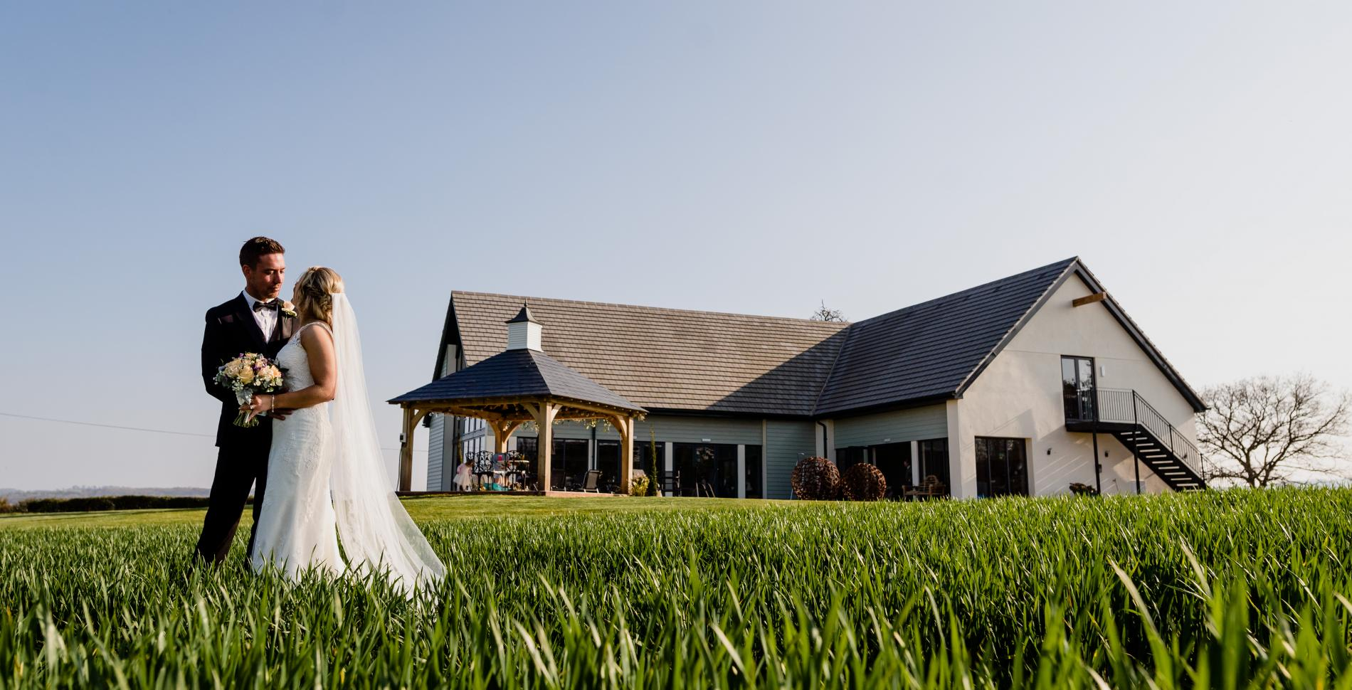 Wedding couple with Harefield Barn in the background